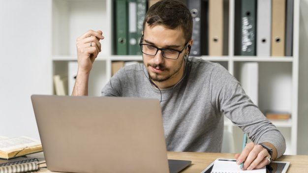 medium-shot-guy-with-headphones-looking-laptop_23-2148389023.jpg